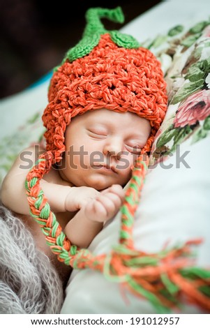 Beautiful baby girl in a knitted hat strawberry - stock photo