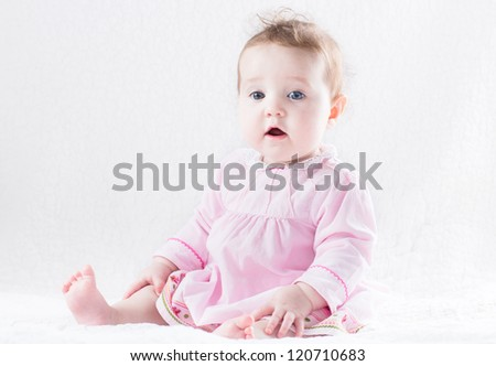 Beautiful baby girl in a pink dress on a white background - stock photo