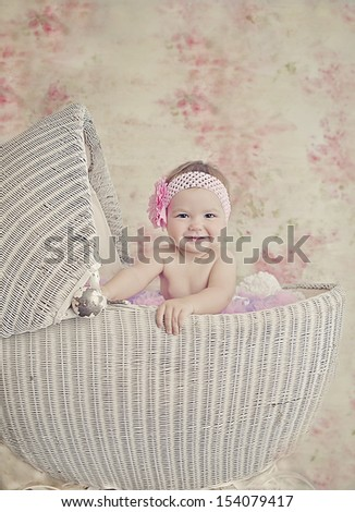 Beautiful baby girl in a vintage stroller - stock photo