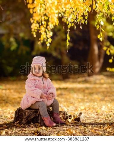 Beautiful baby girl in autumn garden - stock photo