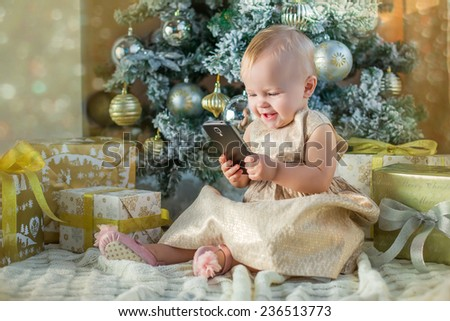 beautiful baby girl in golden dress playing with phone under christmas tree - stock photo