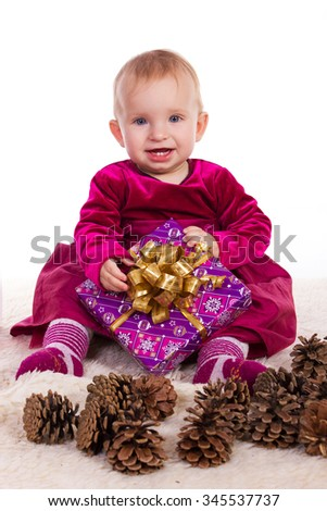 Beautiful baby girl in red dress in New Year's Eve smiling and holding a gift - stock photo