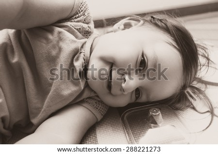 Beautiful baby girl lying down sideways smiling to camera black and white edition - stock photo