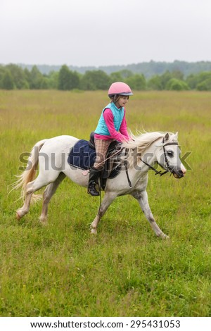 Beautiful baby girl on a white horse galloping across the field - stock photo