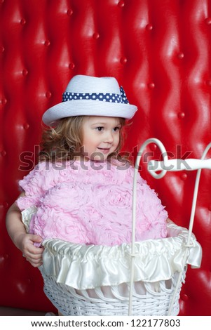 Beautiful baby girl playing with her toy carriage - stock photo