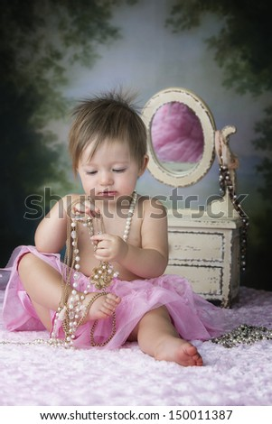 Beautiful baby girl playing with necklaces in front of dresser while wearing a pink tutu - stock photo