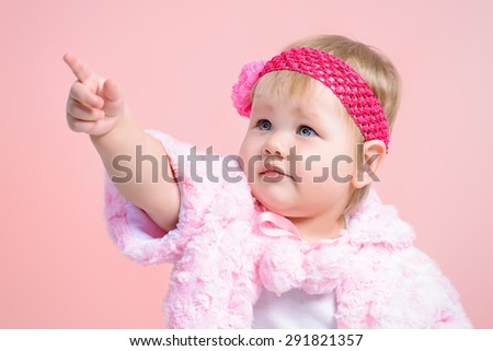 Beautiful baby girl shows a finger on something. Newborn. Happy childhood. - stock photo