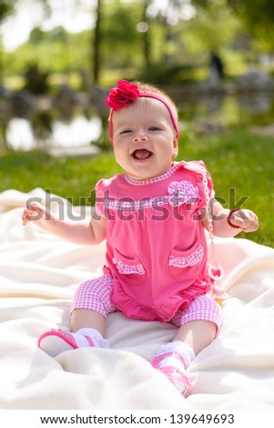 Beautiful baby girl sitting in park - stock photo
