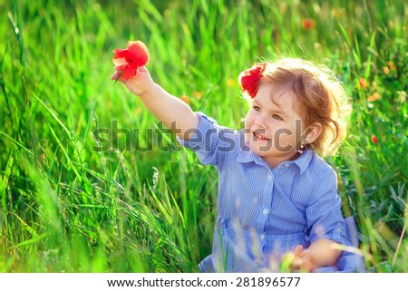 Beautiful baby girl walking in a sunny garden with a flower - stock photo