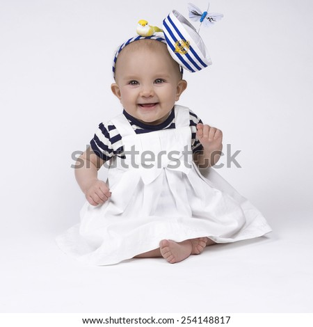 beautiful baby girl wearing a sailor outfit and smiling - stock photo