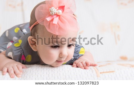 Beautiful baby girl with flower on head crawling - stock photo