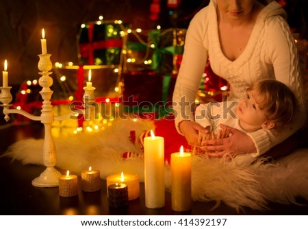 Beautiful baby girl with mother near a Christmas tree with gifts - stock photo