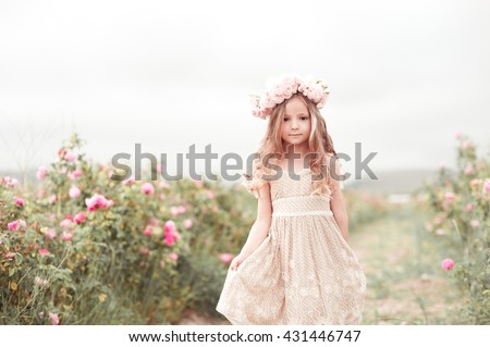 Beautiful baby girl 3-4 year old walking in rose garden with wreath of flowers outdoors. Looking at camera. Childhood. - stock photo