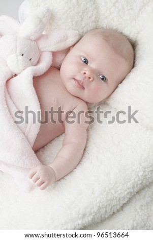 Beautiful baby lying on soft fur textured blanket with pink toy bunny rabbit, vertical layout with copy space. - stock photo