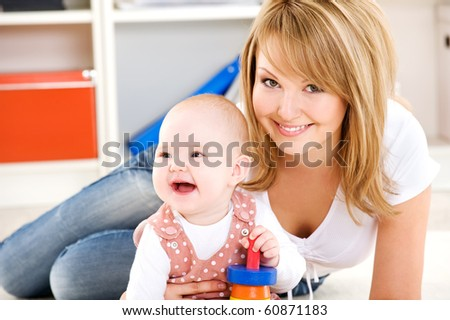 Beautiful baby playing with toys with happy mother  indoors - stock photo