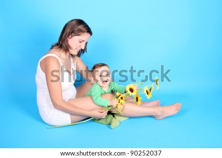 beautiful baby with mother and sunflowers - stock photo