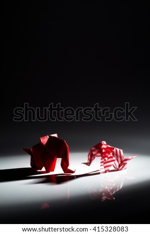 Beautiful back light scene of red origami elephants isolated on black background - stock photo
