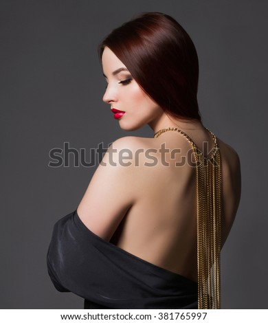 beautiful back of young woman in a black sexy dress.beauty brunette Girl with a necklace on her back.Elegant fashion glamor photo - stock photo