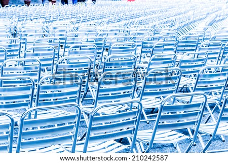 Beautiful background from rows of empty metal chair seats in blue light installed for some business event or concert,performance,festival - stock photo