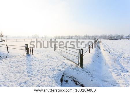 Beautiful background image of a snowy winter landscape with an open gate leading into an empty farm paddock as the rising sun casts its rays over the pristine white snow - stock photo