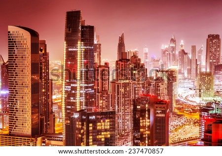 Beautiful background of Dubai at night, gorgeous cityscape over pink sky, many glowing lights of tall skyscrapers, luxury modern expensive architecture design - stock photo