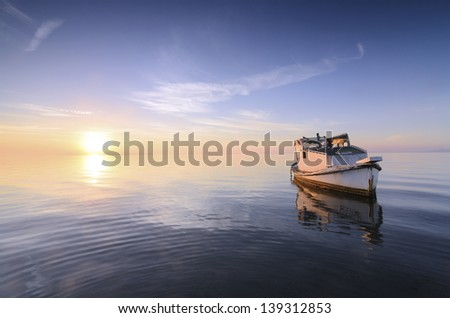 Beautiful background of sky and sea at sunrise with a little old boat abandoned in the Mar Menor, Spain - stock photo