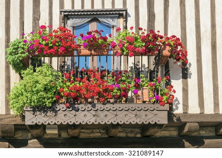 beautiful balcony decorated with red geraniums - stock photo