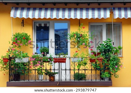 Beautiful Balcony Flowery Garden Close-up And Yellow Residential Building Concrete Wall In The Background - stock photo