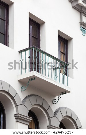 beautiful balcony with a window on white building - stock photo