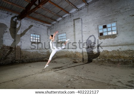 Beautiful ballerina in white dancing and jumping high in the air in abandoned building. - stock photo