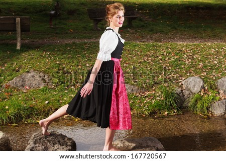 Beautiful barefoot woman playing in a mountain stream in a traditional German dirndl as she enjoys nature /Beautiful barefoot woman in a dirndl - stock photo