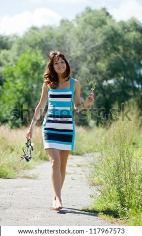 beautiful barefoot woman walking in summer park - stock photo