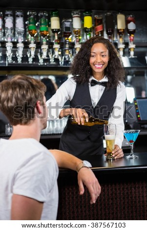Beautiful barmaid pouring beer in glass at bar counter in bar - stock photo