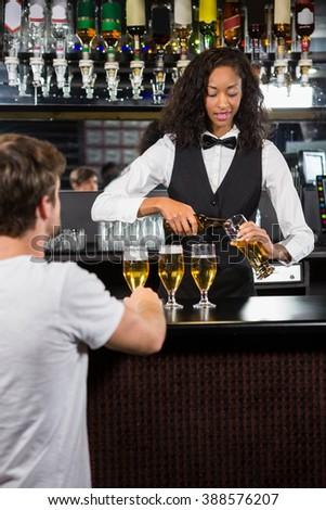 Beautiful barmaid serving beer at bar counter in bar - stock photo
