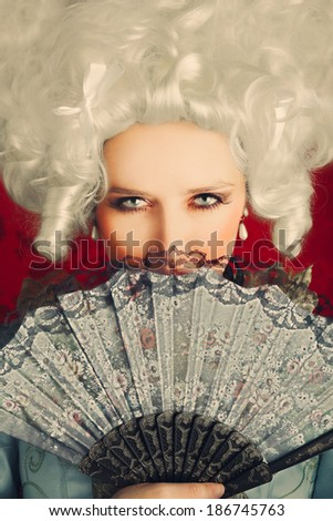Beautiful Baroque Woman Portrait with Wig and Fan - Baroque style portrait of a young beautiful woman behind a hand fan  - stock photo
