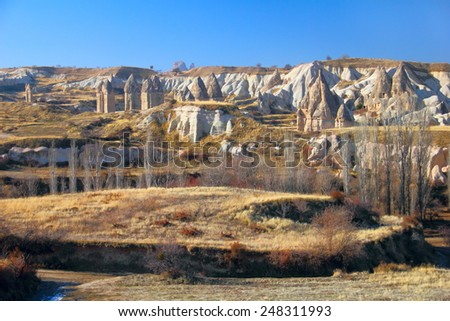 Beautiful barren landscape - ashen mountains (volcanic rocks) - eerie carved and hollowed out structures at the evening in Sward Valley, Goreme, Cappadocia, Central Anatolia, Turkey - stock photo