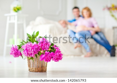 Beautiful basket with a bouquet of flowers is in the interior. The background. Sofa, married couple. - stock photo