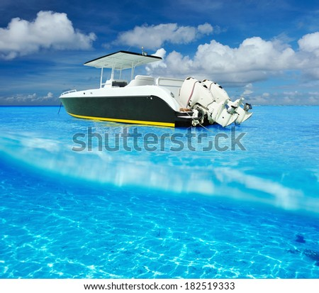 Beautiful beach and motor boat with white sand bottom underwater and above water split view - stock photo