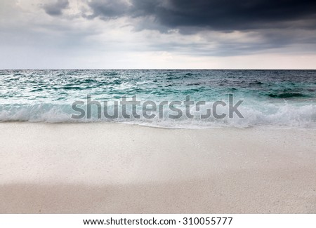 beautiful beach and tropical sea on a stormy day - stock photo