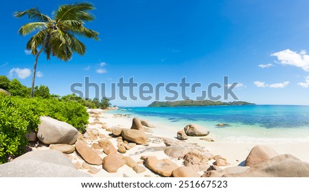Beautiful beach Anse Takamaka seen from the granite boulders, La Digue island, Seychelles. Panorama - stock photo
