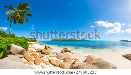 Beautiful beach Anse Takamaka seen from the granite boulders, La Digue island, Seychelles. Panorama - stock photo