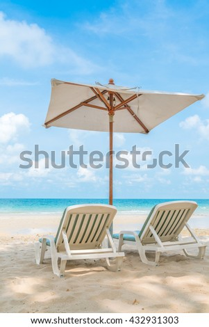Beautiful beach chairs with umbrella on tropical white sand beach - stock photo