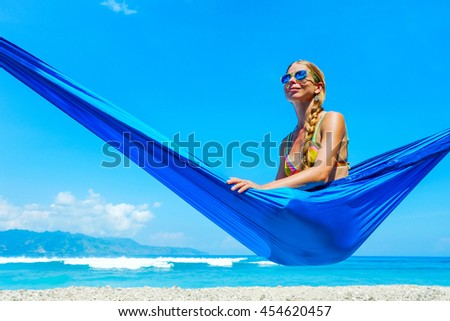 Beautiful beach. Girl relaxing in hammock on the tropical beach. Summer holiday and vacation concept. - stock photo