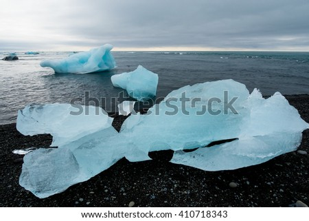 Beautiful beach in the South of Iceland with a black lava sand is full of icebergs. - stock photo
