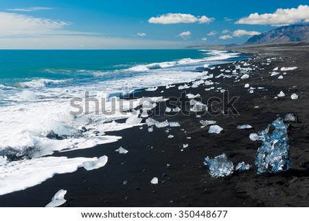 Beautiful beach in the South of Iceland with a black lava sand is full of icebergs from glaciers not far away - stock photo