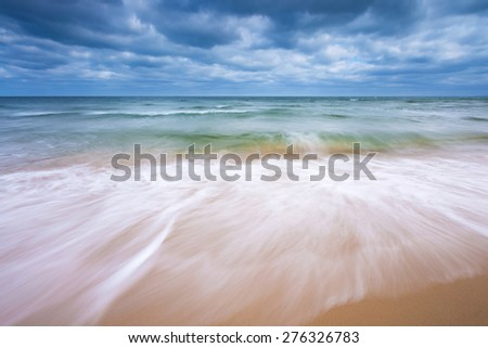 Beautiful beach landscape with cloudy sky and sea with waves. Baltic sea coast near Gdansk in Poland. - stock photo