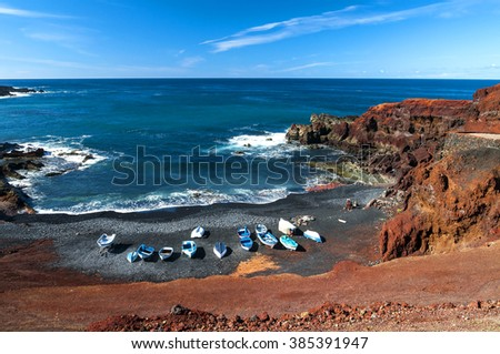 Beautiful beach on the Atlantic Ocean  in the village of El Golfo. A rocky beach with fishing boats surrounded by volcanic mountains / El Golfo bay on the Atlantic Ocean. Lanzarote. Canary Islands - stock photo