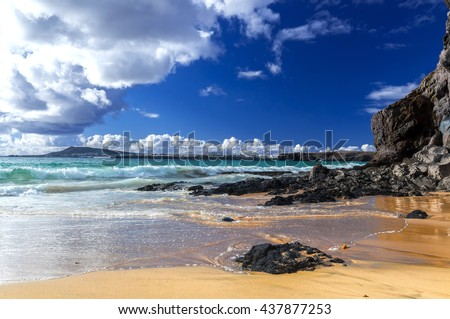 Beautiful beach on the island of Lanzarote in the village Playa Blanca. Sandy beach surrounded by volcanic mountains / Atlantic Ocean and wonderful Papagayo beach. Lanzarote. Canary Islands - stock photo
