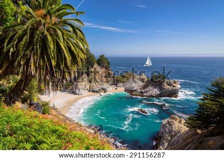 Beautiful beach with palm trees and the white yacht on the horizon.  Julia Pfeiffer beach, Big Sur. California, USA - stock photo