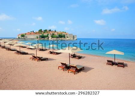 Beautiful beach with sunshades near Sveti Stefan island in Montenegro - stock photo